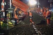SBB-Mitarbeiter bauen nachts ein neues Schotterbett und ein neues Gleis am Bahnübergang ein. (Bild: Nana do Carmo (Berlingen, 7. Oktober 2014))