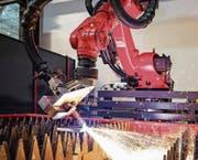Tubenproduktion bei der Permpack AG (oben). Ein Fasenroboter bearbeitet ein Werkstück bei der Stürm SFS AG. (Bilder: zVg)