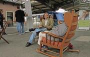 Geschichten erzählen im Schaukelstuhl: Mark Riklin hört einer Frau zu, die mitten auf dem Bahnhofplatz in Romanshorn von einem besonderen Erlebnis mit ihrem Vater erzählt. (Bild: Michèle Vaterlaus)