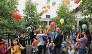 Janine Klingenstein, Leiterin der Tagesschule, und Projektleiter Ueli Wolf lassen inmitten von Kindern bunte Luftballons steigen. (Bild: Manuel Nagel)