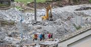 Armeeangehörige und Mitglieder der Bündner Regierung, inmitten der Schäden in Bondo. Die Räumungsarbeiten wurden im Bergsturzgebiet Bergell nach einem neuerlichen Bergsturz aufgenommen. (Bild: KEYSTONE)