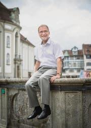 Der Kantonsgerichtspräsident hockt sich auf den Brunnen vor seinem Büro – untypisch spontan. (Bild: Hanspeter Schiess)