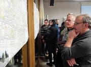 Teilnehmer des Info-Anlasses mustern die ausgehängten Pläne zur Umgestaltung der Dorfdurchfahrt. (Bild: Stefan Hilzinger)