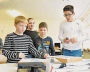 Die Schüler testen ihre selbstgemachte Karte mit den Lämpchen. (Bild: Lukas Hutter)