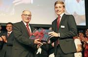 Bankchef Josef Maier erhält von Yves Herzog das Geschenk aller Mitarbeitenden zu seinem 30-Jahr-Dienstjubiläum. (Bild: PD)