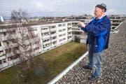 Günter Welte fotografiert vom Dach die Siedlung an der Reutistrasse, die neuen Mehrfamilienhäusern weichen soll. (Bild: Reto Martin)