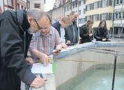 Wie viel Liter fasst der Pankratiusbrunnen und wie gross ist die Wasseroberfläche? Mit diesen und anderen Fragen beschäftigten sich die Teilnehmer der Vernissage. (Bild: Ursula Ammann)