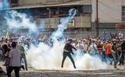 Ein Demonstrant wirft eine Tränengaspatrone zurück an den Absender. (Bild: Miguel Gutierrez/EPA (Caracas, 19. April 2017))