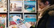 Die Kundin eines Reisebüros studiert einen Ferienkatalog. Noch ist den Schweizern die Reiselust nicht vergangen. (Bild: Michel Canonica)