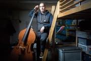 Marc Jenny in seinem Atelier. Hier übt der Künstler mit seinem Kontrabass und am Computer. (Bild: Benjamin Manser (St. Gallen, 14. Dezember 2017))