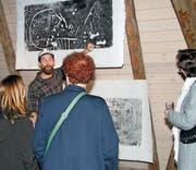 Künstler Patrik Muchenberger erklärt den Vernissagebesuchern die innovative Technik seines Werks. (Bild: Manuela Olgiati)