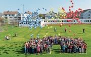 Die Schüler lassen Ballons steigen. Im Hintergrund sieht man die Container, wo der Unterricht während des Baus stattfindet. (Bild: Donato Caspari)