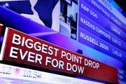 An einem Fernsehbildschirm in der New York Stock Exchange (NYSE) sind am Montag die Nachrichten über den Absturz des Dow-Jones-Indexes zu sehen – er verlor bis Handelsschluss so viel wie noch nie zuvor an einem Tag. (Bild: Keystone)