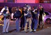 Einsatzkräfte nahe des Tatorts. (Bild: JOHN LOCHER (AP))