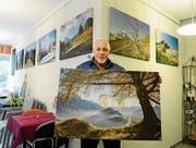 Werner Legler zeigt die Landschaftsbilder aus seinem neuen Kalender an einer Ausstellung im Seecafé in Buchs. (Bild: Hansruedi Rohrer)