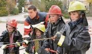 Teamwork: Ein Kind pumpt, das andere löscht mit dem Strahlrohr einen kleinen Brand an einer Hausattrappe. Offizier Ivo Forster gibt Anweisungen. (Bild: Werner Lenzin)