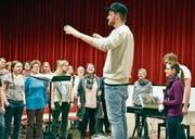 Chorleiter Simon Griesinger dirigiert und wird von Irene Stäheli (3. von rechts) tatkräftig am Klavier unterstützt. (Bild: Nadine Schwizer)