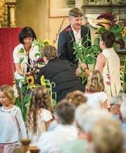 Die Gottesdienstbesucher verabschieden den Pfarrer und seine Frau mit Blumen. (Bild: Reto Martin)