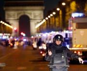Ein massives Polizeiaufgebot sperrt den Champs Elysées nach der Attacke auf Polizisten. (Bild: THIBAULT CAMUS (AP))