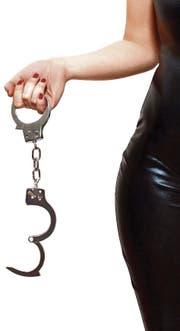 Dominatrix holding handcuffs, isolated on white background (Bild: Alexovics Attila (62014524))