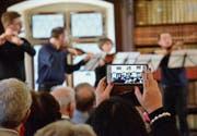 Eine Konzertbesucherin hält eine Momentaufnahme auf ihrem Smartphone fest. (Bild: Christoph Heer)