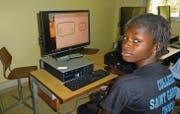 Eine Schülerin in einer Schule im senegalesischen Thiès vor einem Computer mit St. Galler Bildschirm. (Bild: pd)