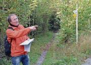 Kantonsarchäologe Hansjörg Brem zeigt beim Kaabrüggli in Tägerschen den Verlauf des historischen Verkehrswegs. (Bild: PD/Markus Zahnd)
