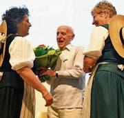 Veteran Willi Sonderegger mit Jahrgang 1921 wird von den Ehrendamen mit Blumen und einem Glas Honig beschenkt. (Bild: Fritz Heinze)
