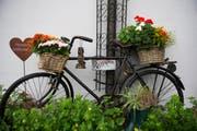 Ein mit Blumen dekoriertes Velo, daneben ein rostiges Herz. (Bild: Urs Jaudas)