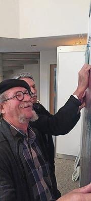 Die Kirchberger Künstler Rolf Klaus und Erich Brocker hängen ein Bild für die Charity Gallery auf. (Bild: PD)