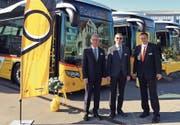 Von links: Walter Schwizer, Florian Jud und Claudio Albrecht vor den neuen Hybridpostautos. (Bild: Postauto)