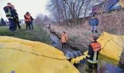 Feuerwehrmann Florian Eugster steht mehr als knietief im Wasser, während es Ruedi Jungen hinter der Sperre nur bis zu den Knöcheln reicht. (Bild: Manuel Nagel)