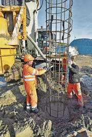 Die Bauarbeiter versenken ein rund 20 Meter langes Armierungsgitter ins mit Beton gefüllte Bohrloch. Polier Beat Meili kontrolliert mit der Wasserwaage die Neigung des Eisens. (Bild: Mario Testa)
