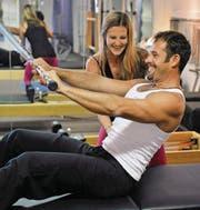 Roll down: Trainerin Fabienne Stacher zeigt ihrem Partner Andreas Tobler eine Bauchübung. (Bild: Reto Martin)