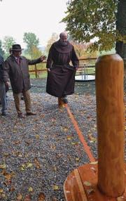 Wallfahrtspriester Raphael Fässler balanciert über das elastische Band, unterstützt von Kirchenratspräsident Jürg Grämiger.