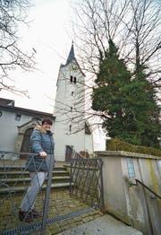 Daniela Müller, Vizepräsidentin der Kirchgemeinde, vor der Kirche. Rechts zwei der alten Bäume, die gefällt werden müssen. (Bild: Mario Testa)