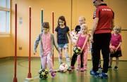 Dribbling um Stangen: Die Mädchen üben unter Anleitung von Trainer Urs Spiri die Ballführung. (Bild: Reto Martin)