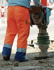 Ein Bauarbeiter mit einem Stampfer am Werk. (Bild: Reto Martin.)