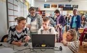 Jugendliche erklären Erwachsenen in der Schule Goldach das Spiel Finance Mission Heroes. (Bild: Michel Canonica)