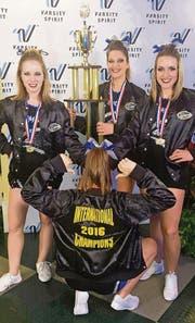 Die Cheerleaderinnen Tamara Kühne, Liza Kern, Nadine Pfister und (mit dem Rücken zur Kamera) Seray Öznalci präsentieren den Pokal. (Bild: pd)