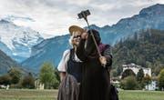 Eine Touristin mit Niqab in Interlaken macht ein Selfie mit einer Frau in Tracht. (Bild: Rolf Neeser/Keystone (Interlaken, 4. Oktober 2017))