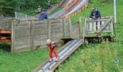 Buntes Treiben auf der Skisprungschanze Chollersweid in Wildhaus: Auch bei strömendem Regen erklimmen die einen die Stufen und freuen sich auf den bevorstehenden Flug, während der nächste Sportwoche-Teilnehmer bereits in der Anlaufspur ist. (Bild: Robert Kucera)
