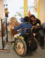 Der 19jährige A. K. freut sich über die Klänge, die er mit dem Becken und dem Gong erzeugen kann. Musiktherapeutin Dodo Trieblnig begleitet ihn mit der Gitarre und ihrem Gesang. (Bild: Larissa Flammer)