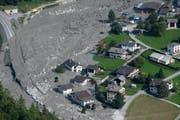 Die Luftaufnahme zeigt das Material des Felssturzes, das bis ans Dorf geschoben wurde. (Bild: GIAN EHRENZELLER (EPA KEYSTONE))