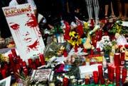 Vor dem Liceu Theater in Barcelona legen Passanten Blumen und Kerzen für die Opfer nieder. (Bild: QUIQUE GARCIA (EPA))