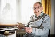 Enoch Habisreutinger in seinem Büro, wo er alle Ordner mit Briefmarken, Postkarten und Stempeln aufbewahrt. (Bild: Reto Martin)