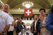 AUNS-Mitglieder singen an einer Hauptversammlung die Nationalhymne. (Bild: PETER KLAUNZER (KEYSTONE))
