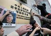 Demonstranten bringen nach dem ersten Verschwinden des Verlegers Gui Minhai 2016 dessen Porträt am Gebäude der chinesischen Regierung in Hongkong an. (Bild: Vincent Yu/AP (3. Januar 2016))