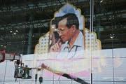 Arbeiter befestigen ein Porträt des verstorbenen thailändischen Königs Bhumibol am Flughafen der Hauptstadt Bangkok. (Bild: Keystone)