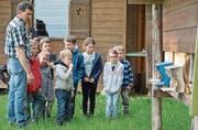 Imker Ernst Fuchs zeigt den Kindern die Einfluglöcher zu seinem Bienenhaus oberhalb des Golfplatzes in Lipperswil. (Bild: Mario Testa)
